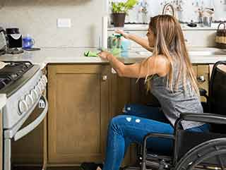Young disabled woman on a wheelchair cleaning the kitchen and doing house chores by herself