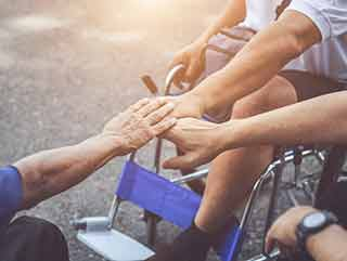 3 people touching hands, one in a wheel chair.