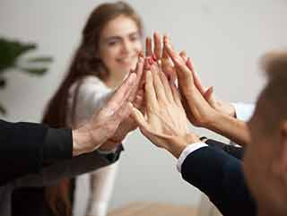 Group of people touching hands, excited about professional care coordination